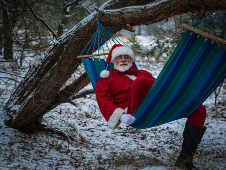 Santa Claus lies relaxed in the hammock in the winter forest. Christmas vacation.