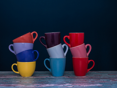 Three chrome piles of cup of coffee of different colors on the dark blue background. Concept of togetherness.