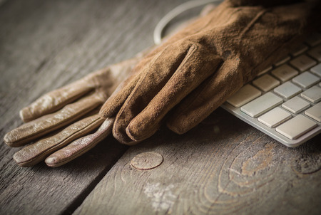 he: Leather and suede brown gloves and  keyboard on the rude tableÑŽ he and she, agreement Stock Photo