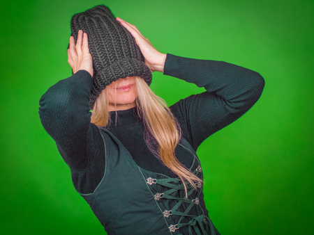 Woman with green clothes holds his head with his hands.