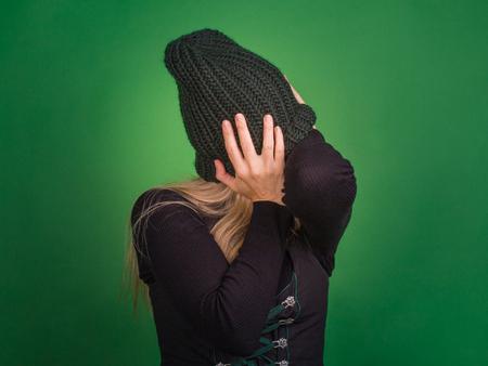 Conceptie van emotie, isolatie. Vrouw bedekt haar gezicht met een gebreide muts, houdt zijn hoofd met zijn handen. Ze luistert niet, sloot hun oren met hun handen. Stockfoto