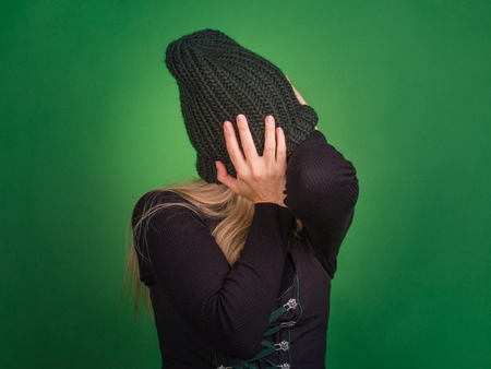 Conception of emotion, isolation. Woman covers her face with a knitted hat, holds his head with his hands. She do not listen, closed their ears with their hands. Archivio Fotografico