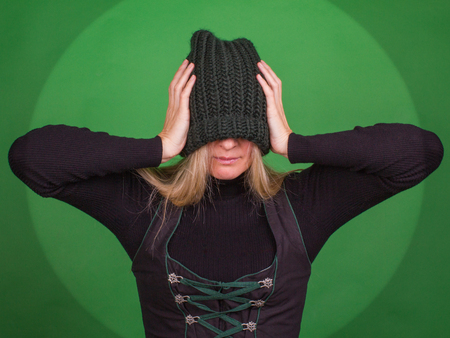 Young woman covers her face with a knitted hat and holds his head with his hands. Supression concept.