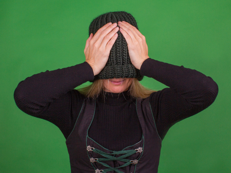 Young woman covers her face with a knitted hat and holds his head with his hands. Consept isolation.