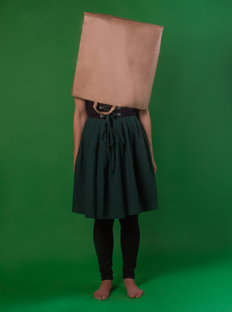 Woman with bare feet and a paper bag on her head, standing on a green background dressed in a dark clothes, vertical, conceptual, simple