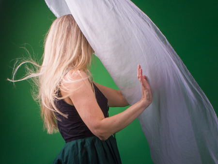 Blonde woman withholds white silk against the light