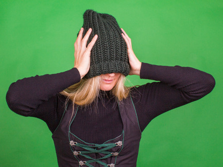 Rubia con un gran sombrero hecho punto sostiene su cabeza con sus manos