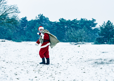 Snow landscape,Santa Claus  carrying a heavy bag to children. Stock Photo