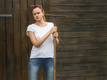 Young farm worker is standing by a wooden shed, holding a rake and looking serious at the camera