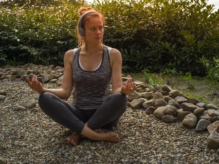 De aantrekkelijke jonge vrouw met een lang haar en hoofdtelefoons op haar hoofd in Yoga stelt het praktizeren in tuin. Stockfoto