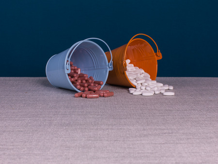 Pills in two pails on the table and dark blue background.