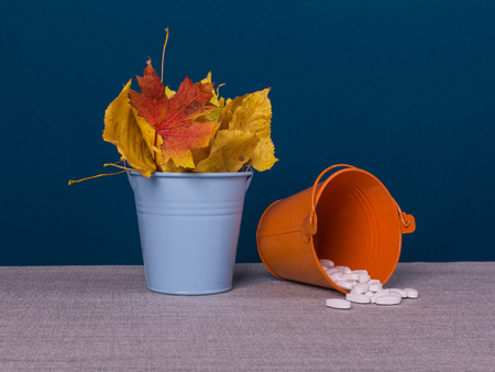 Two pails with pills and full with autumn leaves on the table, blue background. Stock Photo