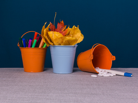 Three pails with pills, autumn leaves and colored markers on the table, blue background.