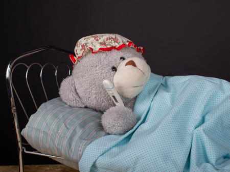 oneself: Eepidemic concept. Sick teddy bear lying in bed with a temperature. Black background, closeup.