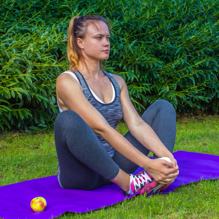 Sporty woman sits right in tension- nature, apple,