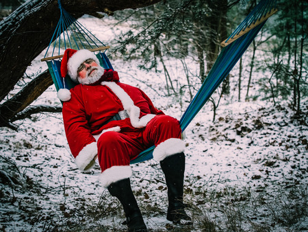 Santa Claus rested in the hammock in the winter forest. Christmas vacation. Comfort , overwork, calm down concept.