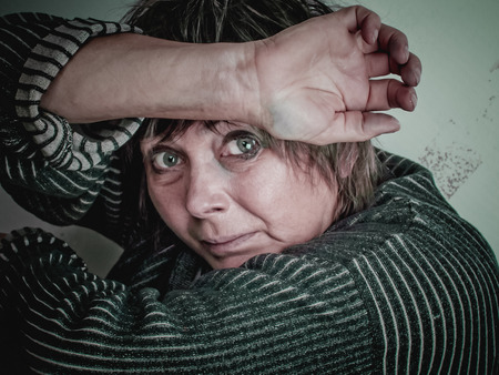 Fearful women of middle age hopelessly closed her face with her hands.