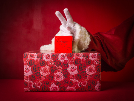 Hand of Santa Claus with two fingers up in the peace or victory symbol and two gift boxes on the red background.