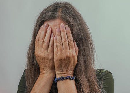 Desperate woman with a closed face in a confined space. Emotions and probleems concept. Imagens