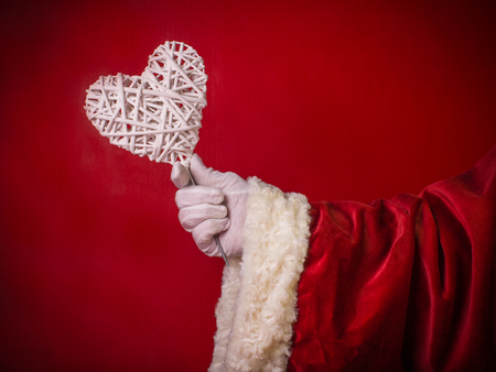 Hand of Santa Claus with a white heart .Close up, on the red background.Concept love in a relations. Stock Photo