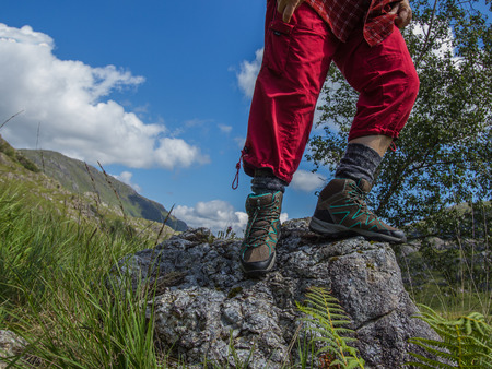 Fragment of the foots, sports shoes for trekking close up on a background of landscape with mountains.