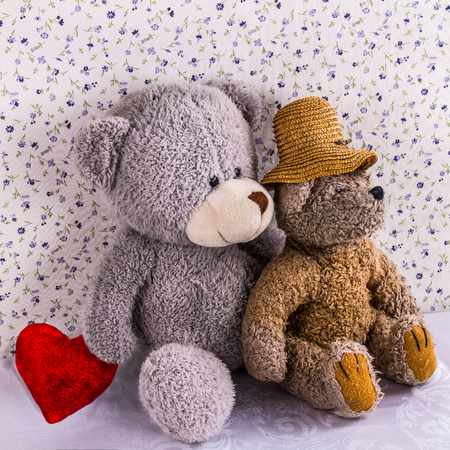 Two enamored teddy bears sit next to with red plush heart on the background of old fashioned wallpaper .