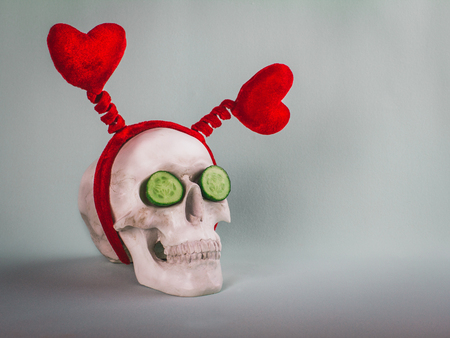 Amusing funny skull with two red hearts and two cucumbers on the soft turquoise background. Healthy Valentines day! Stock Photo