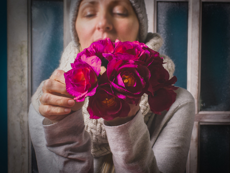 Woman keeps in her hands purple flowers on the foreground close-up, winter with love concept