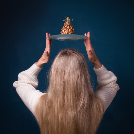 A woman with blond long hair holds above her head a plate with golden pineapple on a dark blue background
