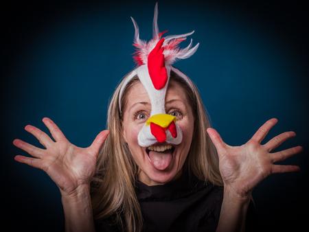 Eine schöne emotionale glückliche blonde Frau mit langen Haaren und Maske als Küken. Buntes Studioporträt mit blauem Hintergrund. Osterparty oder Maskeradekonzept