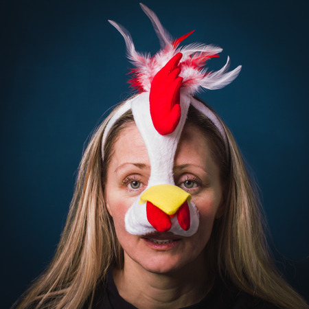 Image of a melancholywoman in chick costume with  sad facial expression, on the blue background.