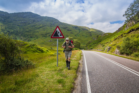 Active man with a red rucksack is walking afoot along a road with a road sign in the mountains of Scotland, summer time. Foto de archivo