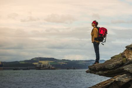 Activity woman  with red rucksack standing on the rocks and looking at the river