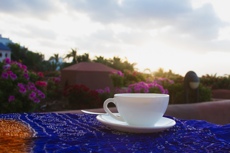 Cup of coffee on a table on the terrace of hotel, over sky background.