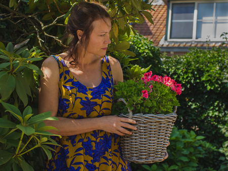 A woman  in her garden with basket of pink flowers. Healthy activity lifestyles concept. Hobby, home, summer.