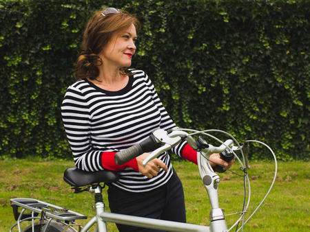 Modern beautiful mature woman with a bike at the park, naturel green background Stock Photo