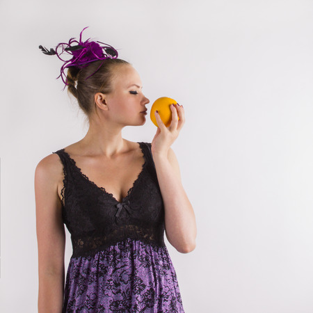 Attractive young woman in violet lingerie sniffing odorous orange,on a white background.