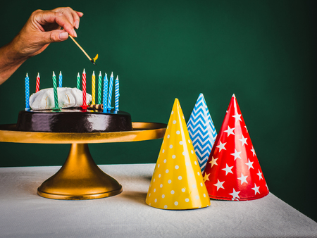 Hand of woman lights the twelve colorful candles in chocolate cake  on golden tray and colored cone caps on the green background.