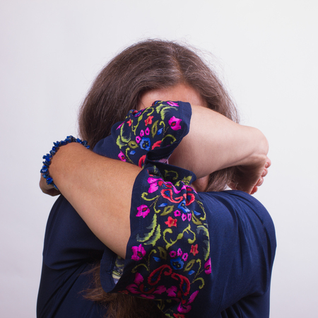 Senior woman in blue dress with pattern closed her face with her hands.