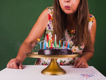 Middle aged woman in summer dress blowing out colorfull candles. Stock Photo