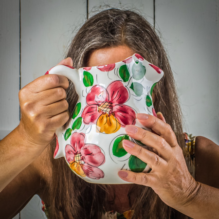 A middle-aged woman at home will hide behind a ceramic jug.