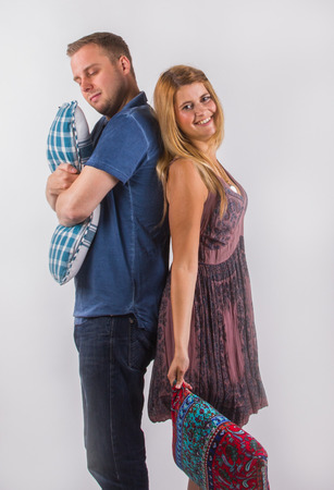 Cheerful young  woman and  serious young man with crossed hands standing back to back with cushions, white background.