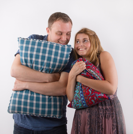 Young man and woman with pillows, funny intimate moments together, white background