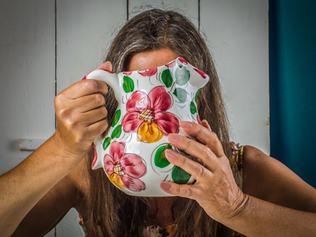 Women of middle age closed her face with a jug.