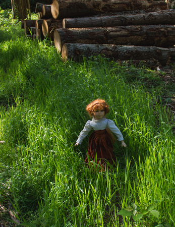 Beautiful vintage doll with red hair standing in sunlight, in green grass, in the forest alone Stock Photo