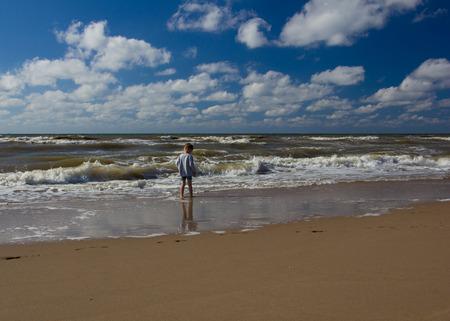 Wholesome kid meet  sea waves on the beach. Big child world, curiosity.