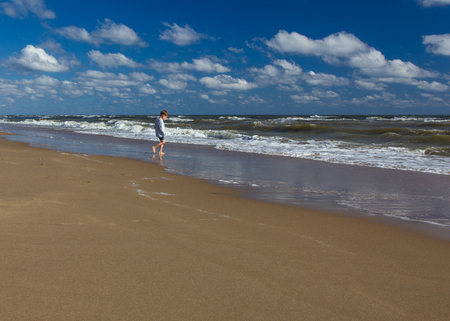 An inquisitive small boy walking along a deserted beach in sea water. Seacoast, horizon, clouds,  blue sky