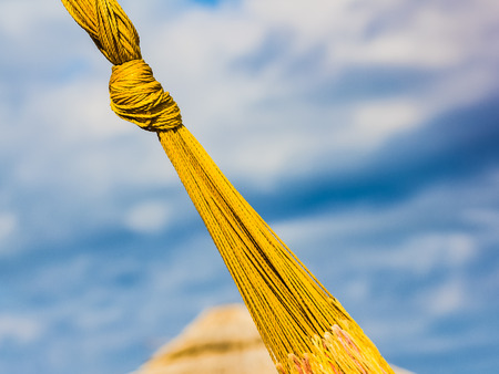 Yellow knot of hammock on the  blue sky background with text message space, diagonal composition