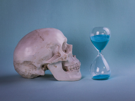 Skull  with sand time on a blue background with copy space. Sand running through the bulbs of an hourglass measuring the passing time.
