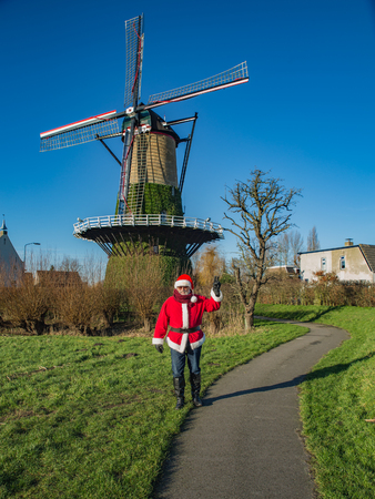 Salutation of Santa Claus from province Brabant of Netherlands, view of countryside with typical Dutch mill.